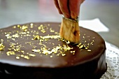 Decorating a chocolate cake with gold leaf