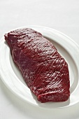Raw fillet of venison on white plate