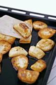 Roast potatoes on baking tray with spatula