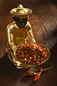 Statuette with bowl of chilli flakes, chillies on wooden background
