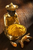 Gilded statuette with ground turmeric and turmeric root
