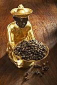 Gilded statuette with tailed pepper in and in front of bowl