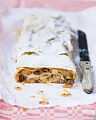 Apple strudel with a slice removed, on paper