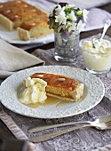 Almond cake with cream and honey, flowers in background