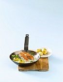 Salmon steak with herb sauce & potatoes in grill frying pan