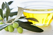 A small bowl of olive oil with an olive sprig