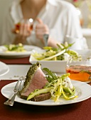 A slice of roast beef with herbs