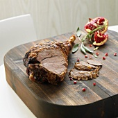 Roast leg of lamb and pomegranate on wooden table