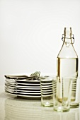 Cutlery, pile of plates, bottle of water and glasses