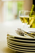 Pile of plates, cutlery and glasses of white wine