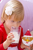 Little girl drinking milk and holding a biscuit in her hand