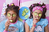Two girls with cucumber slices on their eyes eating cucumber slices