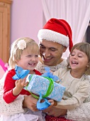 Man in Santa hat holding two girls and gift in his arms