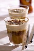 Two glasses of espresso with chocolate-nut liqueur and cream