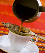 Pouring Turkish coffee through a strainer