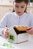 Girl making a gingerbread house for Christmas