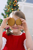 Girl holding two Christmas biscuits in front of her eyes