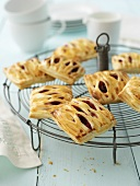 Puff pastries with quark and jam filling on cake rack