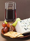 Blue cheese, crackers, grapes, glass of red wine on plate