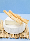Camembert with savoury sticks on straw mat