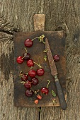 Morello cherries on old chopping board with knife
