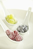 Sugared raspberries, blueberries and grapes on spoons
