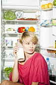 Young woman with bottle of milk sitting in front of opened fridge