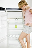 Young woman standing in front of almost empty refrigerator