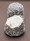 Chocolate teacakes covered in grated coconut (one partly eaten)