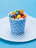 Jelly beans in a beaker on paper plate