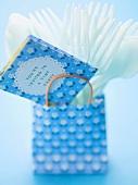 Einladungskarte und Plastikbesteck in Papiertüte