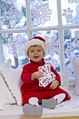 Little girl in Santa costume sitting by window