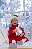 Kleines Mädchen im Nikolauskleid sitzt vor dem Fenster