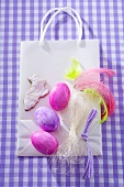 Easter eggs, Easter Bunny biscuit, feathers on paper carrier bag