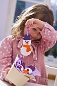 Mädchen hält Schneemann-Baumanhänger aus Salzteig