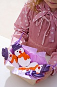 Girl holding a box of salt dough snowmen (tree ornaments)