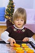Kleines Mädchen legt Orangenscheiben auf ein Backblech