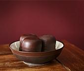Three chocolate teacakes in brown bowl