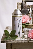 Thermos flask, sage leaves and roses