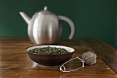 Green tea leaves, tea infuser and teapot
