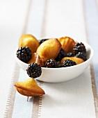 Madeleines with blackberries on cocktail sticks