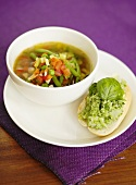 Vegetable soup and bread roll topped with pesto