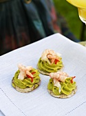 Guacamole and prawns on crackers