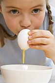 Child blowing a raw egg