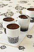 Chocolate cream in four beakers