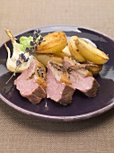 Slices of roast lamb with roasted potatoes and garlic