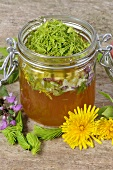 Spruce tips and flower petals in and beside a jar of honey