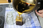 Pouring dandelion syrup into jars