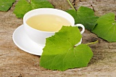 A cup of tea with coltsfoot leaves