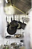 Iron frying pans on hooks by extractor in restaurant kitchen